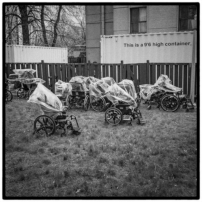 Photo en noir et blanc représentant plusieurs fauteuils sur une pelouse, devant une barrière et des containers blancs. Ils sont couverts d'un sac plastique. Ils représentent les morts du covid19 en institution spécialisé en Ontario. Crédit photo : John Hryniuk http://www.instagram.com/Johnhryniukphotography